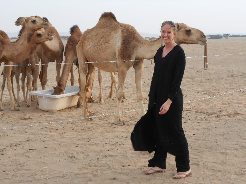PhD student Maggie Johnson at a camel farm in Saudi Arabia.
